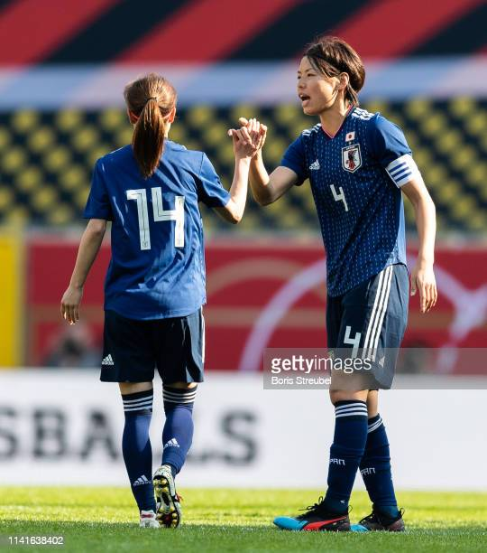 Yui Hasegawa of Japan shake hands with Saki Kumagai of Japan after she scores her team's first goal during the Women's International Friendly match...