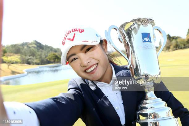 Yui Kawamoto of Japan imitates a selfie as she poses with the trophy after winning the AXA Ladies Golf Tournament at the UMK Country Club on March 31...