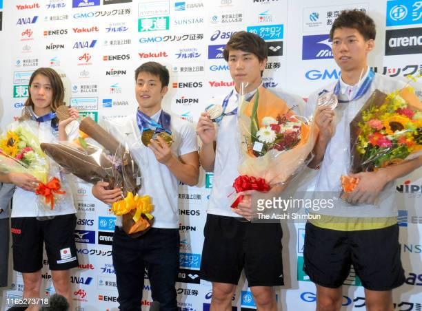 Yui Ohashi Daiya Seto Katushiro Matsumoto and Ippei Watanabe of Japan pose with their medals on arrival at Haneda Airport on July 29 2019 in Tokyo...