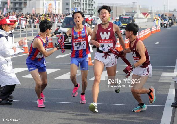 Yuichi Fukuda , 4th runner of Soka University receives the sash from the 3rd runner Yoshiki Haratomi while Ryunosuke Chigira , 4th runner of Waseda...