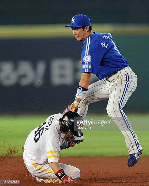Yuichi Honda of Japan's champions Softbank Hawks slides into the second base as Son JooIn of South Korea's champions Samsung lions jumps during the...