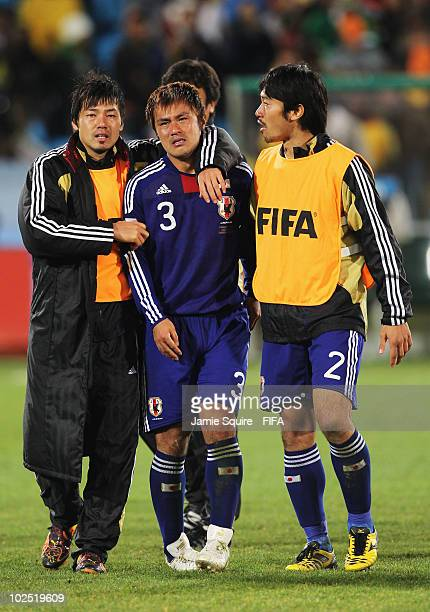 Yuichi Komano of Japan is comforted after missing a penalty during the penalty shoot out during the 2010 FIFA World Cup South Africa Round of Sixteen...