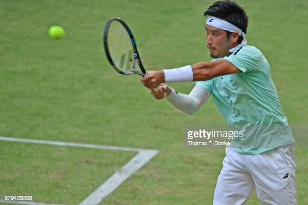 Yuichi Sugita of Japan plays a backhand in his match against Dominic Thiem of Austria during day three of the Gerry Weber Open at Gerry Weber Stadium...