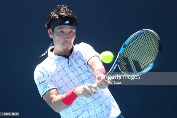 Yuichi Sugita of Japan plays a backhand in his second round match against Ivo Karlovic of Croatia on day three of the 2018 Australian Open at...