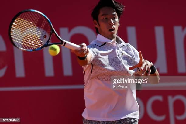 Yuichi Sugita of Japan returns a ball to Juan Martin Del Potro of Argentine during the Millennium Estoril Open 1st round tennis tournament in Estoril...