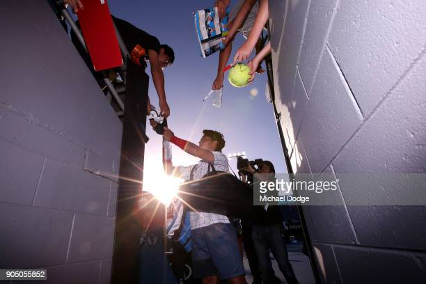 Yuichi Sugita of Japan signs autographs for fans after winning his first round match against Jack Sock of the United States on day one of the 2018...