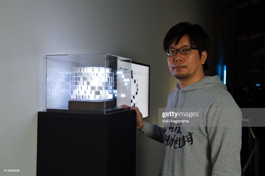 Yuichiro Katsumoto poses for a photograph at the Media Ambition Tokyo at Roppongi Hills on February 8, 2018 in Tokyo, Japan. Artwork details. CD Prayer is a Buddha statue designed to pprevive CD music. The CD will work as a halo of Buddha and give hi-fi music and enlightenment to the people. Robotype, the project and devices to display a letter and to visualize its time and movement simultaneously, invented from the notion that a letter is the trajectory of movement and time - we have to move our body and spend some time - rather than just two-dimensional static symbols for communication.