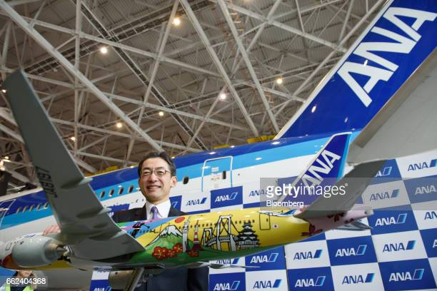 Yuji Hirako president and chief executive officer of All Nippon Airways Co poses with a aircraft model during an initiation ceremony at the company's...