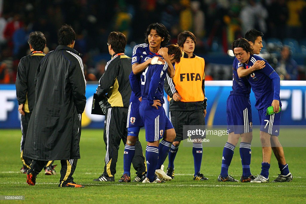 Yuji Nakazawa of Japan (C) consoles Yuichi Komano after he missed in a penalty shoot-out during the 2010 FIFA World Cup South Africa Round of Sixteen match between Paraguay and Japan at Loftus Versfeld Stadium on June 29, 2010 in Pretoria, South Africa.