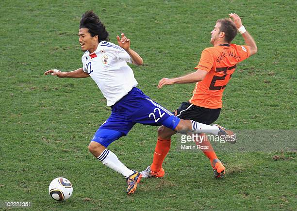 Yuji Nakazawa of Japan falls to the ground after a challenge by Rafael Van der Vaart of the Netherlands during the 2010 FIFA World Cup South Africa...