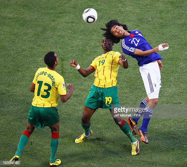 Yuji Nakazawa of Japan is challenged by Stephane Mbia and Eric Choupo Moting of Cameroon during the 2010 FIFA World Cup South Africa Group E match...