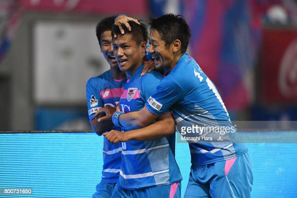 Yuji Ono of Sagan Tosu celebrates scoring the opening goal with his team mates Akito Fukuta and Yoshiki Takahashi during the JLeague J1 match between...