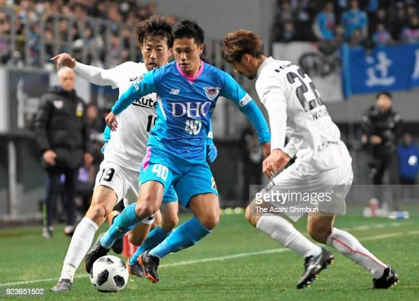 Yuji Ono of Sagan Tosu competes for the ball against Kazuma Watanabe and Wataru Hashimoto of Vissel Kobe during the JLeague J1 match between Sagan...