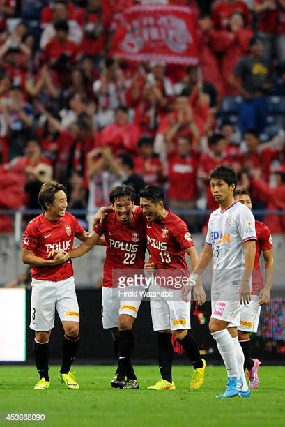 Yuk Abe of Urawa Red Diamonds celebrates scoring his team's first goal with his teammates Tomoya Ugajin and Keita Suzuki during the J. League match...