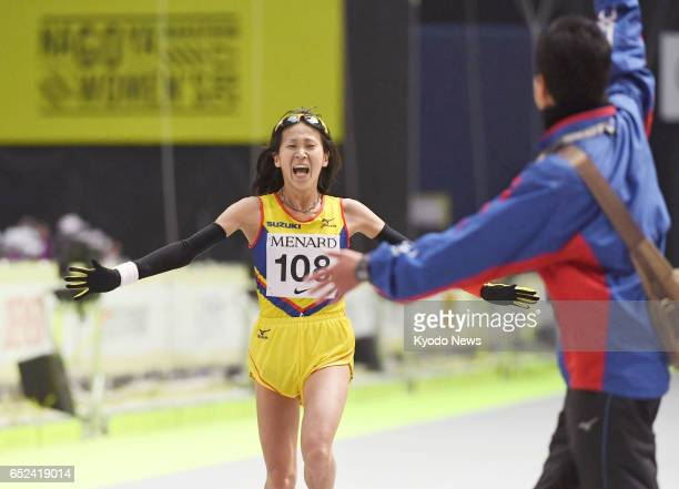 Yuka Ando of Japan crosses the Nagoya Women's Marathon finish line as her coach readies to congratulate her in the central Japanese city of Nagoya on...