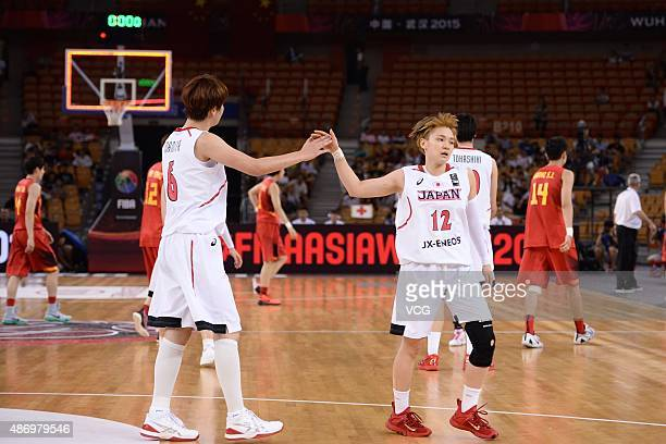 Yuka Mamiya of Japan claps hands with Asami Yoshida of Japan in finals match between Japan and China during the 2015 FIBA Asia Championship for Women...