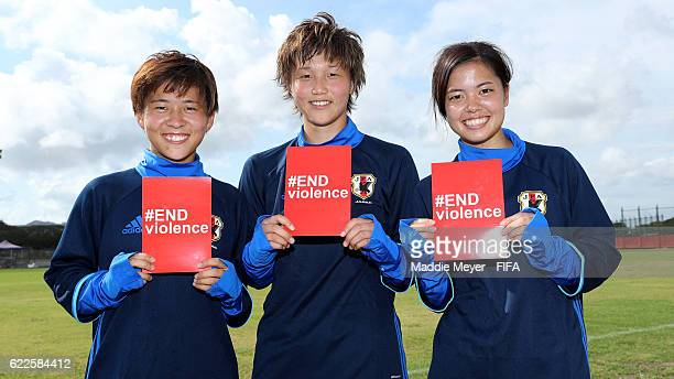 Yuka Momiki of Japan, Ruka Norimatsu, and Yui Hasegawa hold cards supporting the #ENDviolence campaign during a training session in the lead up to...