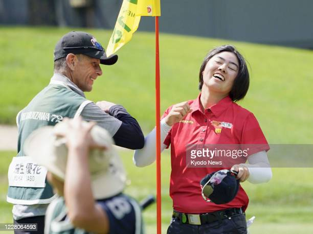 Yuka Saso bumps elbows with her caddie after completing her final round of the NEC Karuizawa 72 golf tournament in Karuizawa in Nagano Prefecture,...