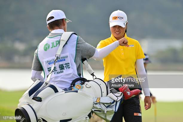 Yuka Saso of Japan elbow bumps with her caddie after holing out on the 18th green during the first round of the JLPGA Championship Konica Minolta Cup...