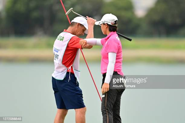 Yuka Saso of Japan elbow bumps with her caddie after holing out on the 18th green during the third round of the JLPGA Championship Konica Minolta Cup...