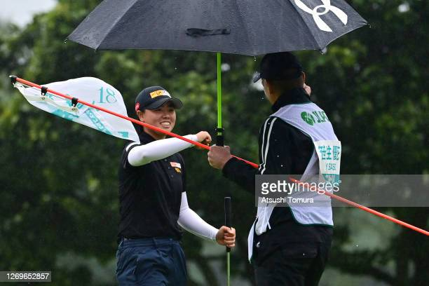 Yuka Saso of Japan elbow bumps with her caddie after winning the tournament on the 18th green during the final round of the Nitori Ladies Golf...