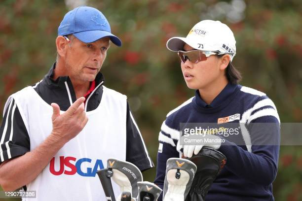 Yuka Saso of Japan talks with her caddie, Lionel Matichuk, on the 12th hole during the second round of the 75th U.S. Women's Open Championship at...