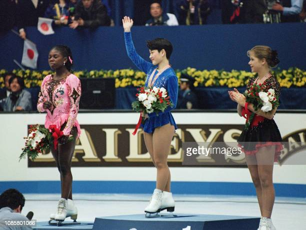 Yuka Sato of Japan and Tanja Szewczenko of Germany wave to the crowd as silver medalist Surya Bonaly of France stands idle on the podium at the...