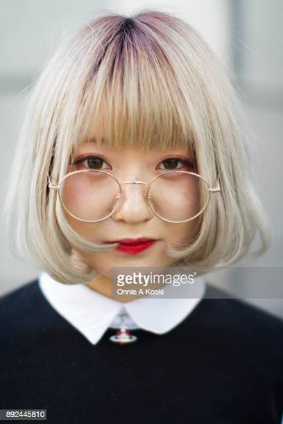 Yuka with dyed blond hair wearing large round brass glasses a black sweater vest a white pointed flat collared shirt a brown and gray plaid skirt and...