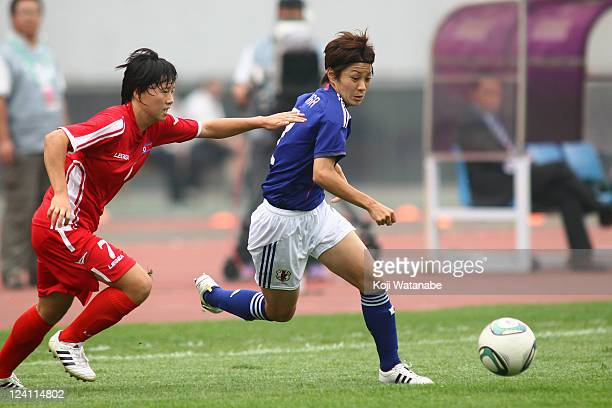 Yukari Kinga of Japan and Ri Ye Gyong of North Korea compete for the ball during the London Olympic Women's Football Asian Qualifier match between...