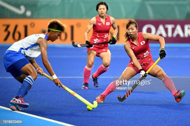 Yukari Mano of Japan is checked by Yang Chiayu of Chinese Taipei during the preliminary round of the Women's Hocky Competition at the Gelora Bung...