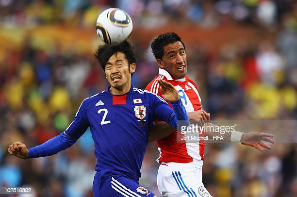 Yuki Abe of Japan jumps for the ball with Lucas Barrios of Paraguay during the 2010 FIFA World Cup South Africa Round of Sixteen match between...
