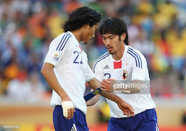 Yuki Abe of Japan puts the captain's armband onto Yuji Nakazawa during the 2010 FIFA World Cup South Africa Group E match between Netherlands and...