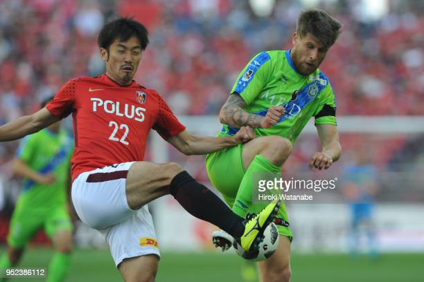Yuki Abe of Urawa Red Diamonds and Alen Stevanovic of Shonan Bellmare compete for the ball during the JLeague J1 match between Urawa Red Diamonds and...