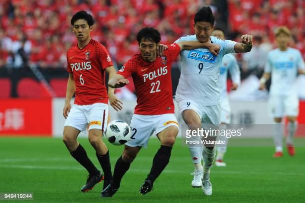 Yuki Abe of Urawa Red Diamonds and Ken Tokura of Consadole Sapporo compete for the ball during the JLeague J1 match between Urawa Red Diamonds and...