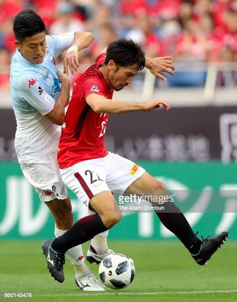 Yuki Abe of Urawa Red Diamonds and Ken Tokura of Consadole Sapporo compete for the ball during the JLeague J1 match bewteen Urawa Red Diamonds and...