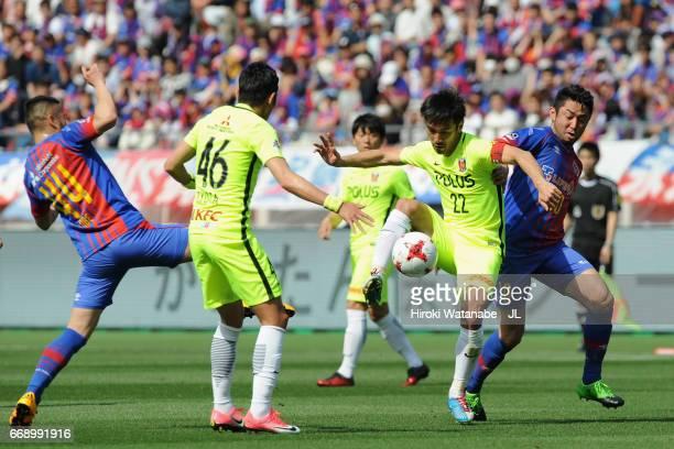 Yuki Abe of Urawa Red Diamonds controls the ball under pressure of Takuma Abe and Yohei Kajiyama of FC Tokyo during the J.League J1 match between FC...