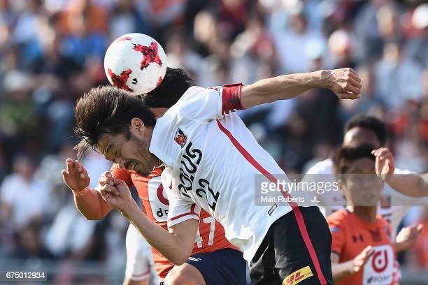 Yuki Abe of Urawa Red Diamonds heads the ball over Yuzo Iwakami of Omiya Ardija during the JLeague J1 match between Omiya Ardija and Urawa Red...