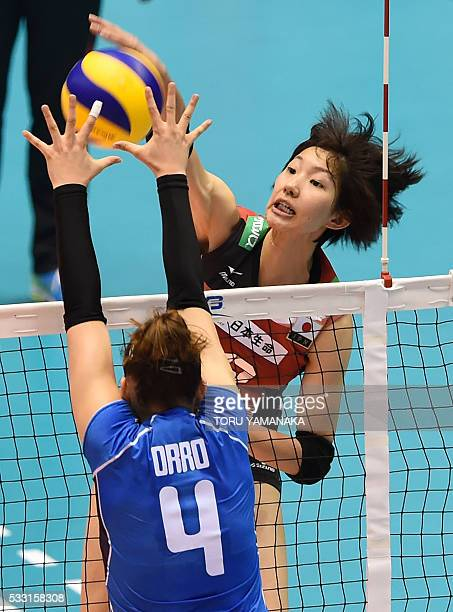 Yuki Araki of Japan spikes the ball over Alessia Orro of Italy during the women's volleyball world final qualification for the Rio de Janeiro...