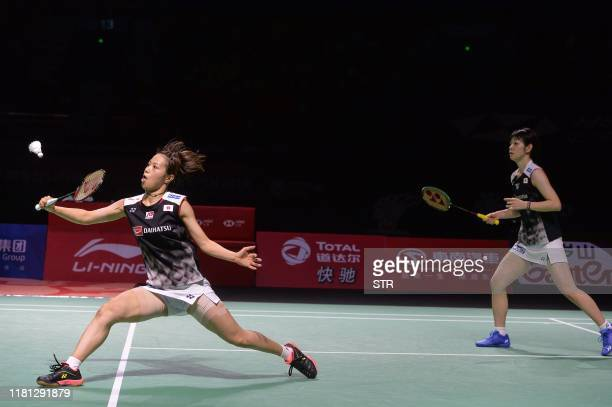 Yuki Fukushima of Japan hits a return beside partner Sayaka Hirota against Lee Sohee and Shin Seungchan of South Korea during their women's doubles...