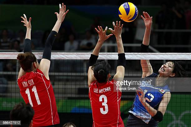 Yuki Ishii of Japan plays a shot in front of Saori Kimura of Korea and Erika Araki of Korea during the Women's Preliminary Pool A match between Japan...