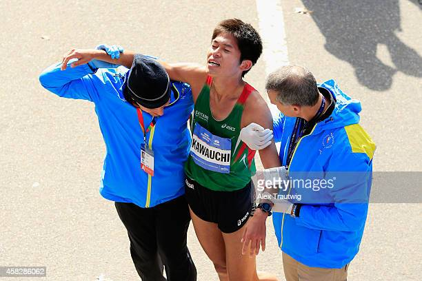 Yuki Kawauchi of Japan is assisted after crossing the finsih line during the Pro Men's division during the 2014 TCS New York City Marathon in Central...