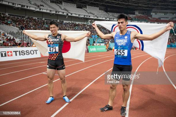 Yuki Koike of Japan celebrates his win with second place Yang Chunhan of Chinese Taipei in the final of the men's 200m athletics event during the...
