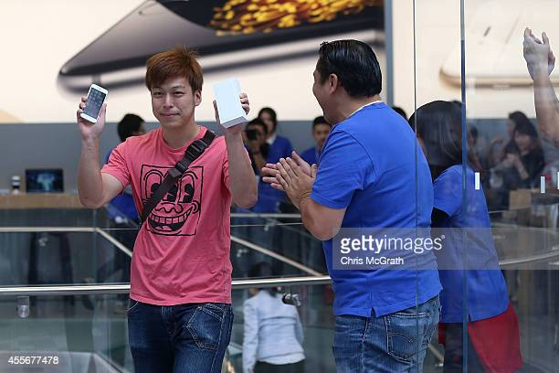 Yuki Manno shows off his new iPhone after being the first person to purchase the new device at the launch of the new Apple iPhone 6 and iphone 6 plus...