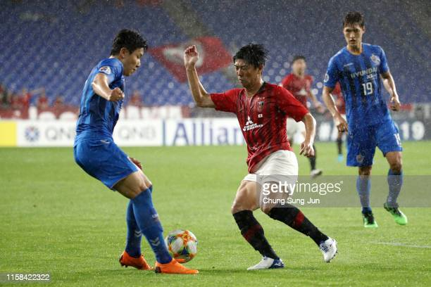 Yuki Muto of Urawa Red Diamonds and Kim In-sung of Ulsan Hyundai compete for the ball during the AFC Champions League round of 16 second leg match...