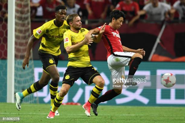 Yuki Muto of Urawa Red Diamonds and Marcel Schmelzer of Borussia Dortmund compete for the ball during the preseason friendly match between Urawa Red...