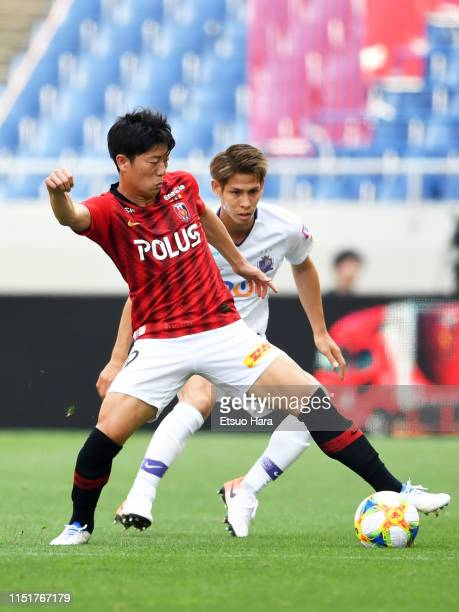 Yuki Muto of Urawa Red Diamonds and Sho Sasaki of Sanfrecce Hiroshima compete for the ball during the J.League J1 match between Urawa Red Diamonds...