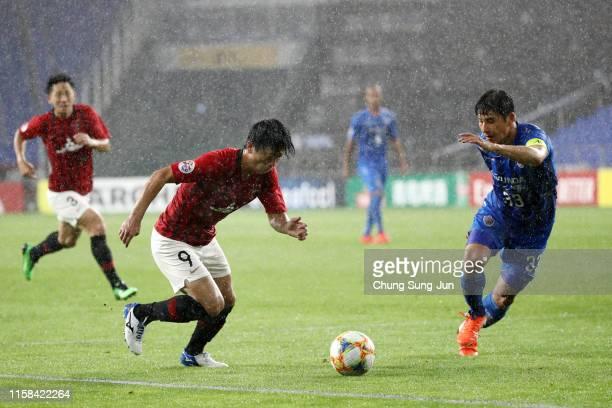 Yuki Muto of Urawa Red Diamonds takes on Park Joo-ho of Ulsan Hyundai during the AFC Champions League round of 16 second leg match between Ulsan...