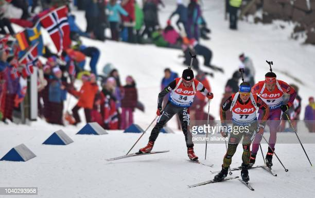 Yuki Nakajima of Japan Erik Lesser of Germany and Tim Burke of USA in action during the men's 20km individual competition at the Biathlon World...