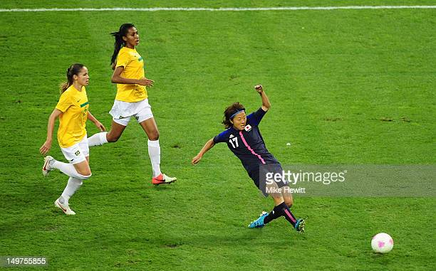 Yuki Ogimi of Japan scores the opening goal despite the efforts of Erika and Bruna of Brazil during the Women's Football Quarter Final match between...