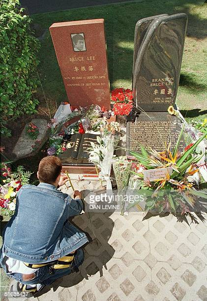 Yuki Shigeoka of Tokyo places incense July 20 at the gravesite of martial arts leader and movie star Bruce Lee at a cemetary in Seattle WA on the day...